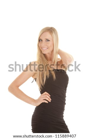 A woman in her black dress with her hand on her neck with a smile. - stock photo