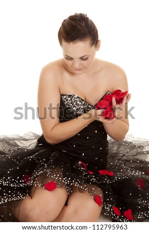 A woman  in her black formal holding a bunch of red rose petals in her hand looking down. - stock photo