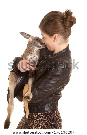 a woman in her black leather jacket getting kisses from her pet kangaroo. - stock photo