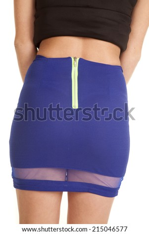 A woman in her black top and blue skirt, showing off the back. - stock photo