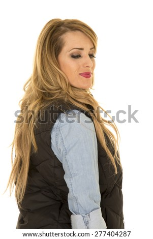 a woman in her black vest and denim looking over her shoulder. - stock photo