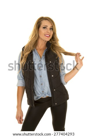 a woman in her black vest, playing with her hair. - stock photo