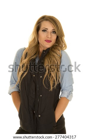 A woman in her black vest trying to stay warm. - stock photo