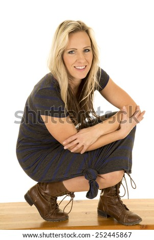 A woman in her boots and dress with a smile on her face. - stock photo