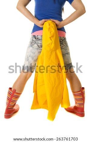 a woman in her bright colored clothes, and rain boots, holding on to her raincoat behind her. - stock photo