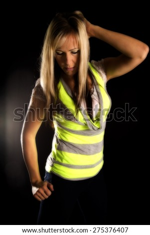 a woman in her bright colored shirt with a serious expression on her face, looking down. - stock photo