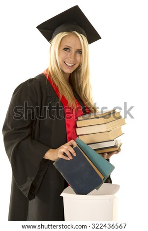 a woman in her cap and gown with a smile, throwing her books away. - stock photo