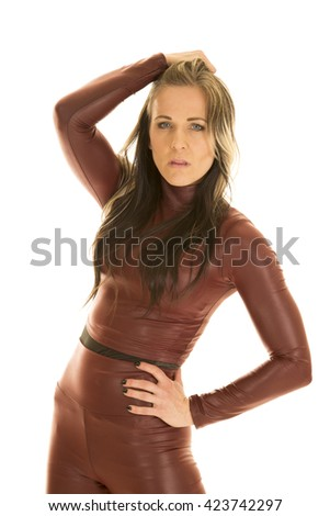 A woman in her dark tight fitted bodysuit with her hand in her hair with a sensual expression. - stock photo