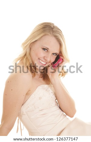 a woman in her fancy dress talking on her cell phone with a smile on her face. - stock photo