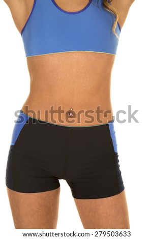 a woman in her fitness clothing showing off her stomach. - stock photo