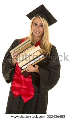 A woman in her graduation gown with a stack of books tipping over. - stock photo