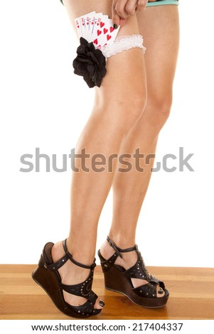 A woman in her heels reaching down in her garter for a playing card. - stock photo