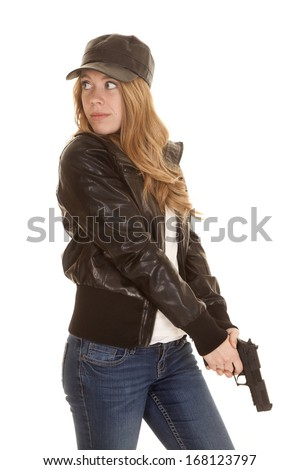 a woman in her leather jacket and hat pointing her gun down. - stock photo