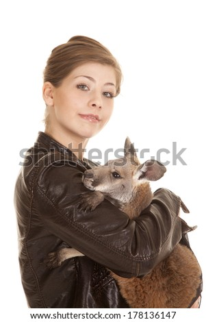 a woman in her leather jacket holding on to her pet kangaroo with a small smile. - stock photo
