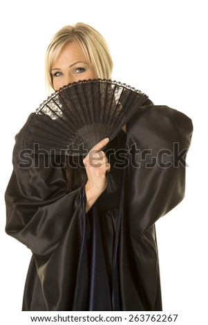 A woman in her medieval dress with a smile, hiding behind a fan. - stock photo