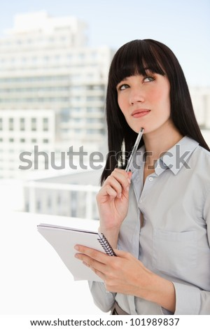 A woman in her office with a notepad and a pen against her chin looks upwards as she thinks - stock photo