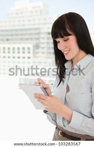 A woman in her office writing down notes on her note pad - stock photo