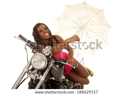 A woman in her pink dress laying on top of her motorcycle, holding on to her umbrella. - stock photo