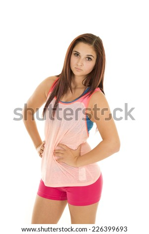 A woman in her pink tank and spankies with her hands on her hips. - stock photo