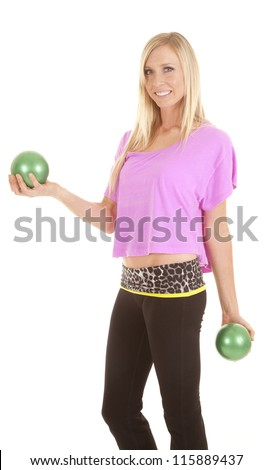 A woman in her pink top and black bottoms holding on to her green ball weights with a smile on her face - stock photo