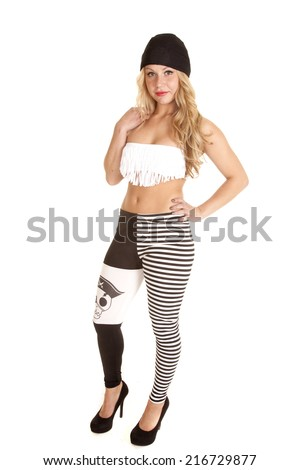 a woman in her pirate leggings and fringe bra, with a serious expression. - stock photo