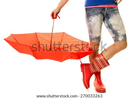 a woman in her rain boots holding on to her red umbrella. - stock photo