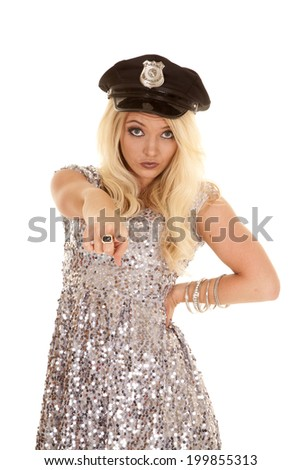 a woman in her silver dress pointing her finger while wearing her police hat. - stock photo