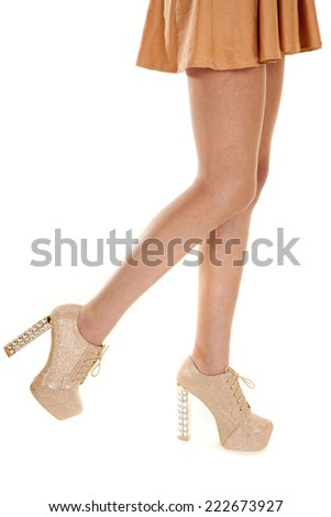 A woman in her skirt and tan heeled shoes walking. - stock photo