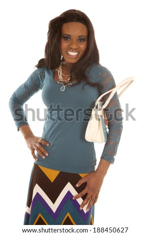 A woman in her skirt holding on to her purse. - stock photo