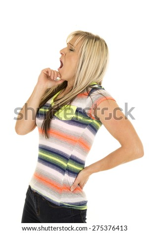 A woman in her striped shirt, yawning with her hand by her chin.  She is tired. - stock photo