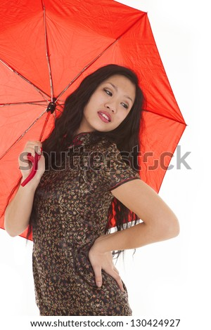 A woman in her traditional Asian clothing holding on to a red umbrella - stock photo