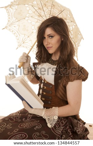 A woman in her vintage dress holding her umbrella while she is reading a book. - stock photo