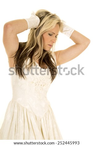 A woman in her vintage white dress, with her hands up in her hair. - stock photo