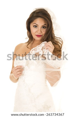 A woman in her wedding dress holding onto her wedding veil. - stock photo