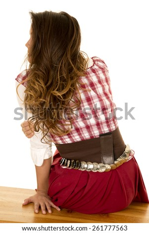 a woman in her western wear, looking over her shoulder sitting. - stock photo