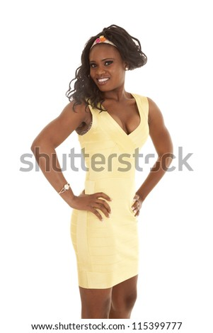 a woman in her yellow dress standing with her hands on her hips with a smile on her lips. - stock photo