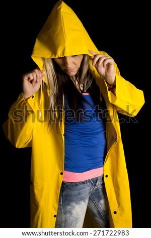 A woman in her yellow rain coat hiding under her hood. - stock photo