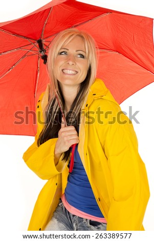 A woman in her yellow rain coat, hiding under her umbrella with a big smile. - stock photo