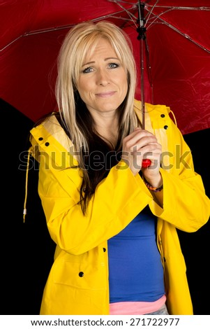 a woman in her yellow rain coat, with a funny expression on her face. - stock photo