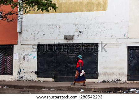 A woman in local dress walking on the street in down town Harare, Zimbabwe - stock photo