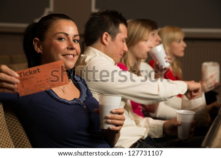 A woman in the audience of a theater, in a concert hall or a cinema presenting a ticket or admission pass - stock photo