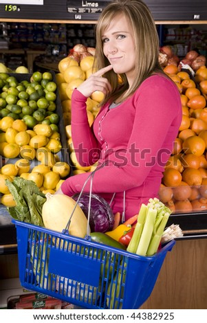 A woman in the grocery store buying fruits and vegetables. - stock photo