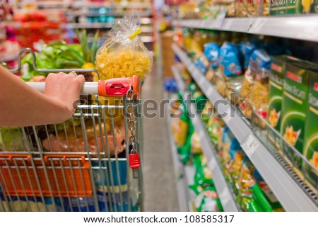 a woman in the purchase of food in a supermarket. everyday life of a housewife - stock photo