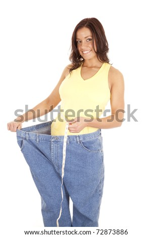 A woman in very large pants is measuring her small waist. - stock photo