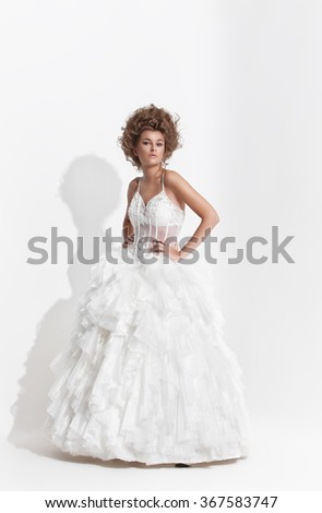 A woman in white wedding dress over white background. - stock photo
