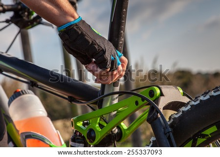 A woman is adjusting the Saddle from her Mountainbike. - stock photo