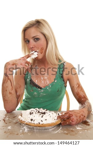 A woman is all messy and has a pie with chocolate and whipped cream. - stock photo