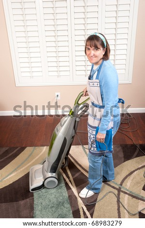 A woman is conducting housework by vacuuming a rug on a wooden floor. - stock photo