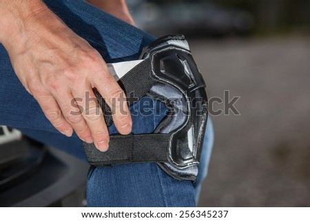 A woman is dressing her inliner protection to her knee. - stock photo