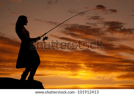 A woman is fishing in the sunset. - stock photo